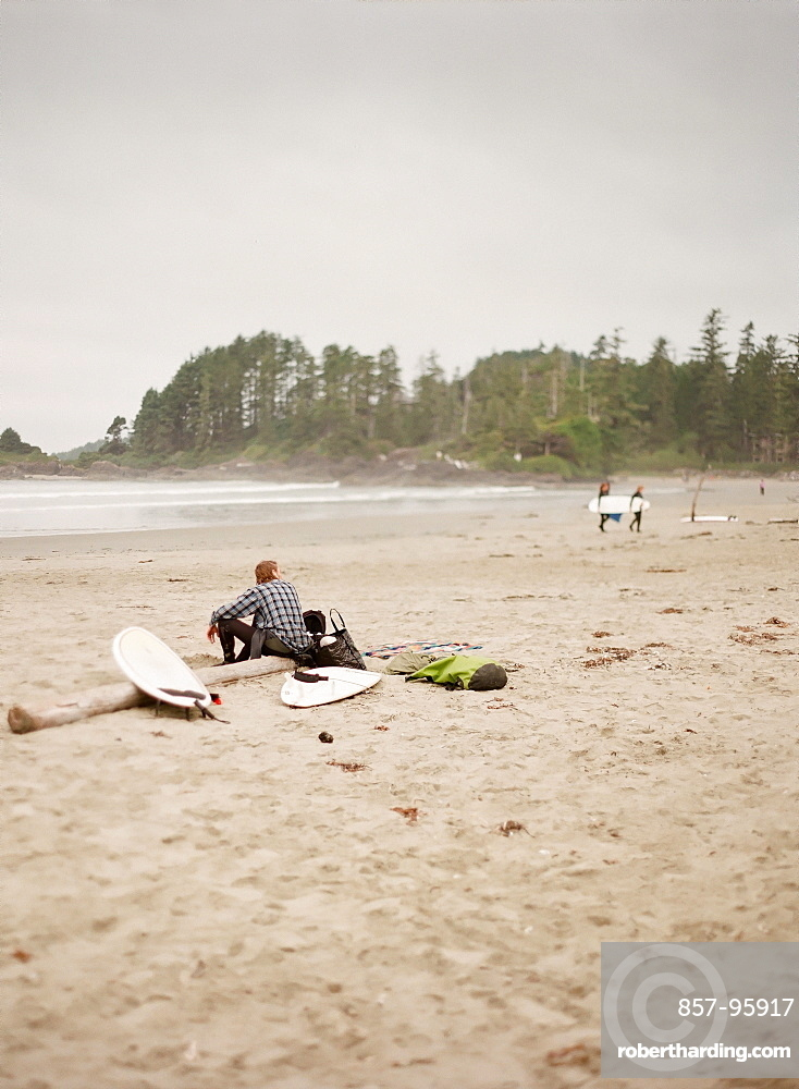 Surfer sitting on log on sandy beach, Vancouver, British Columbia, Canada