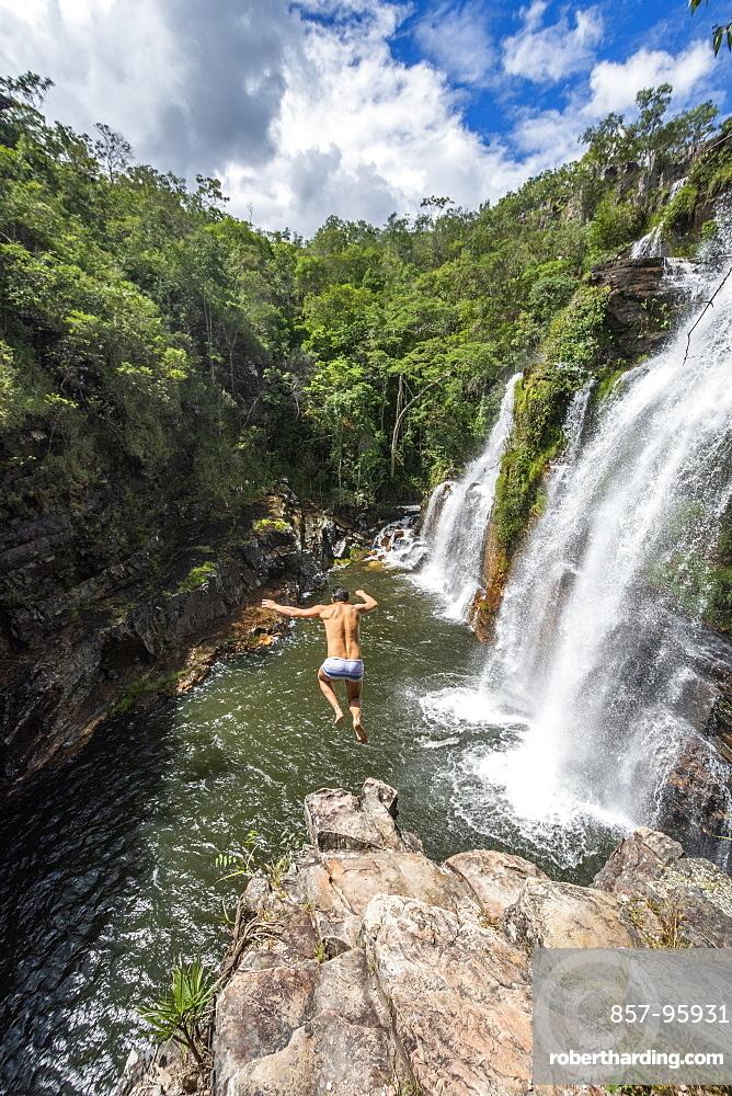View of adventurous man cliff jumping from waterfall in cerrado, Chapada dos Veadeiros, Goias, Brazil