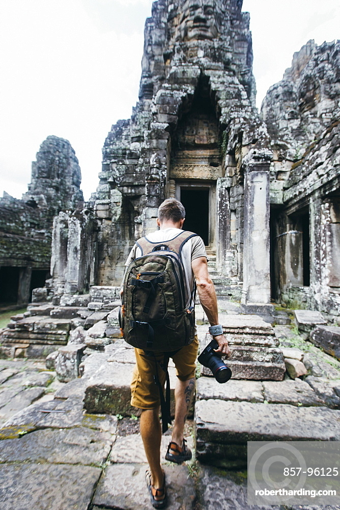 Rear view shot of a single tourist holding a camera exploring ancient Cambodian temple, SiemReap Province, Cambodia