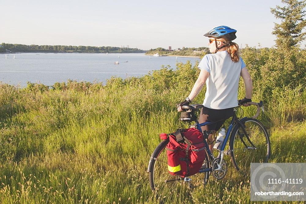 Woman With Bike Along A Lake