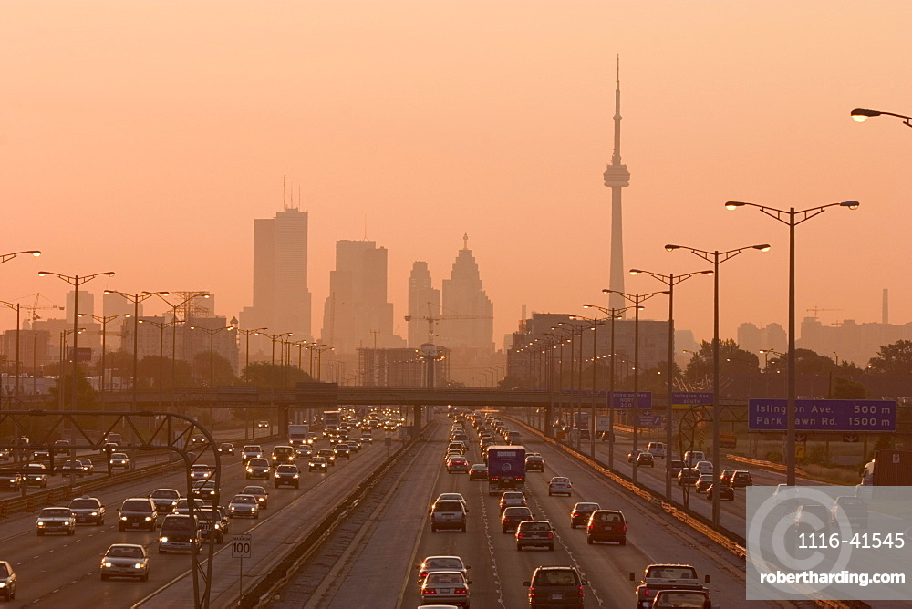 View Of Toronto Skyline From Above Queen Elizabeth Way Highway During Start Of Rush Hour Traffic, Toronto, Ontario, Canada.