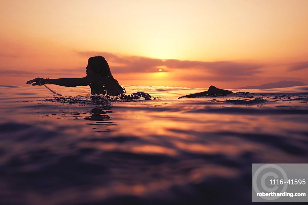 A Woman Paddling On A Surfboard At Sunset, Tarifa, Cadiz, Andalusia, Spain