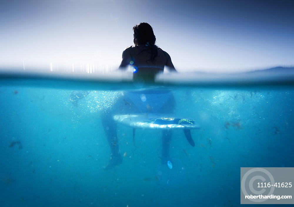 A Woman Sitting On A Surfboard In The Water, Tarifa, Cadiz, Andalusia, Spain