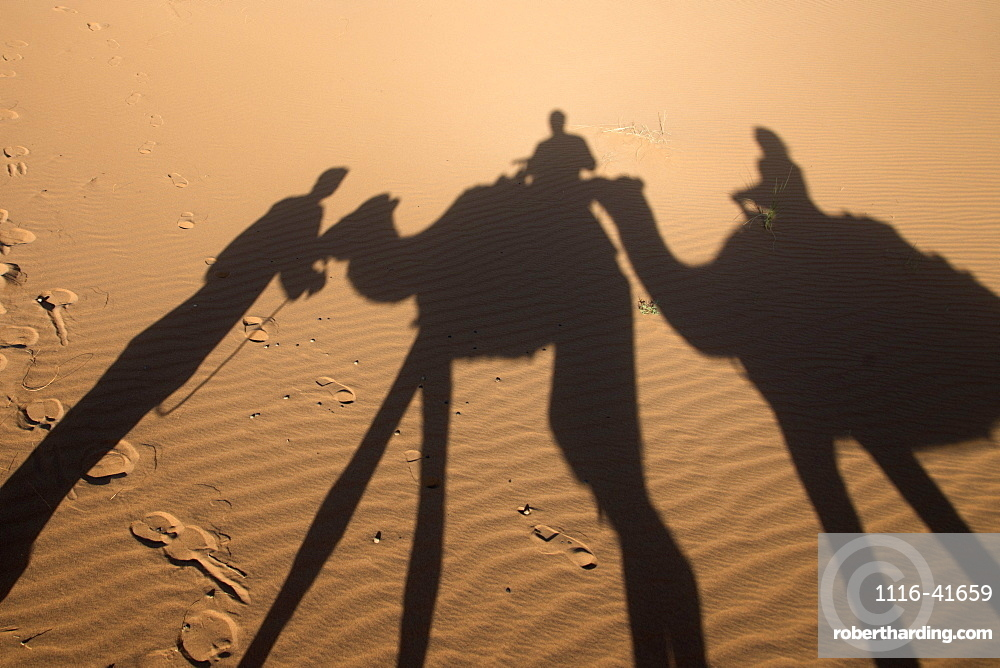 Shadow on the sand of people riding on camels