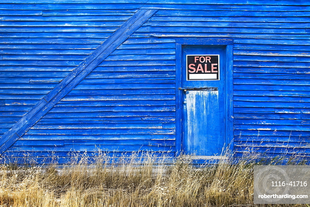 A blue barn with a for sale sign in the window of the door, Saskatchewan canada