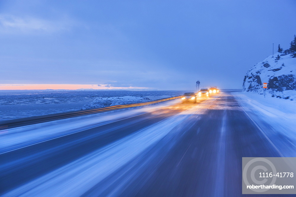 Traffic driving on the seward highway during a snowstorm at twilight in winter, beluga point, Anchorage, alaska, united states of america