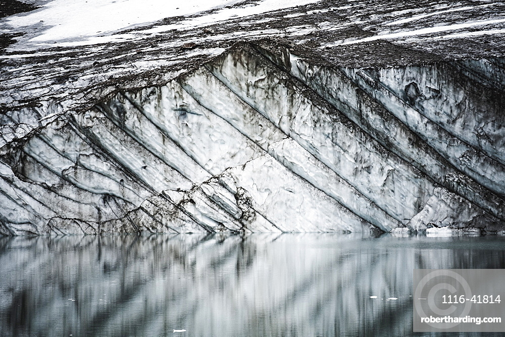 Layers in gravelly glacier cliff reflected in a small glacial lake, jasper national park, Alberta, canada
