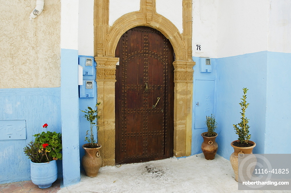 A house with an arched wooden door with rivets and painted blue walls in old town, Rabat morocco