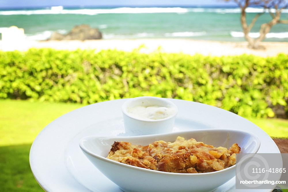 A food item served in a white serving dish with a view of the beach and ocean, Hawaii united states of america