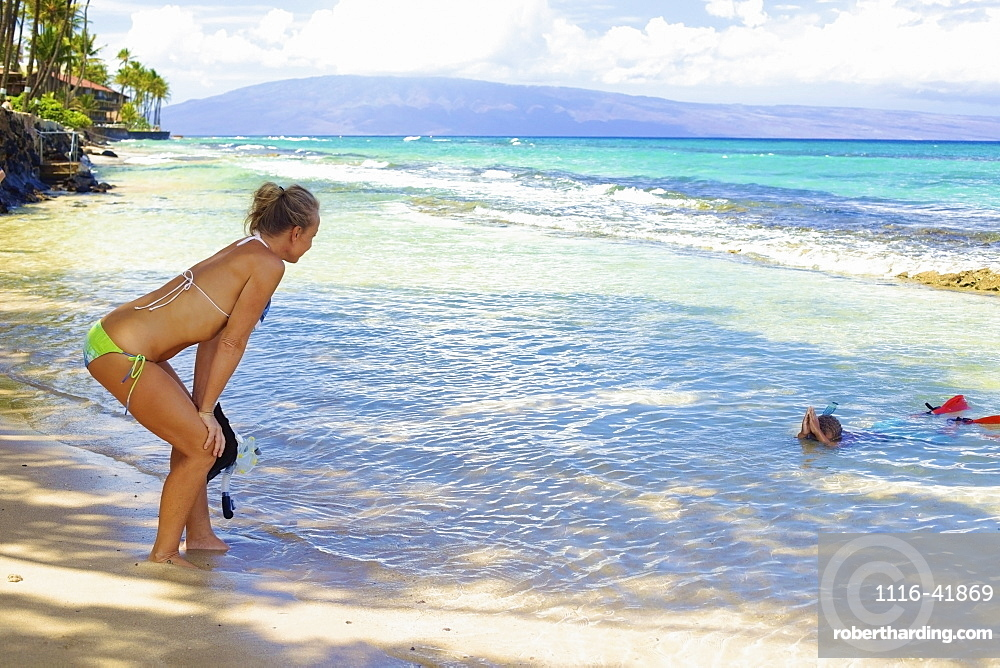 A mother watches her son snorkelling in the shallow water at the beach, Hawaii united states of america