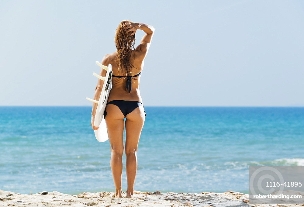 A woman wearing a black bikini stands at the water's edge holding a surfboard, Tarifa cadiz andalusia spain