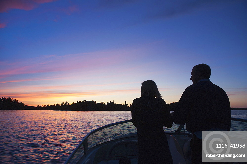 Middle aged couple travelling by motorboat in the lake of the woods at sunset, kenora ontario canada
