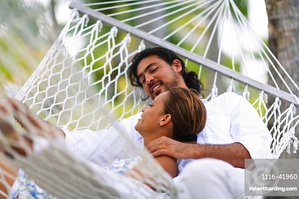 A man and woman in a hammock at the bora bora nui resort and spa, Bora bora island society islands french polynesia south pacific