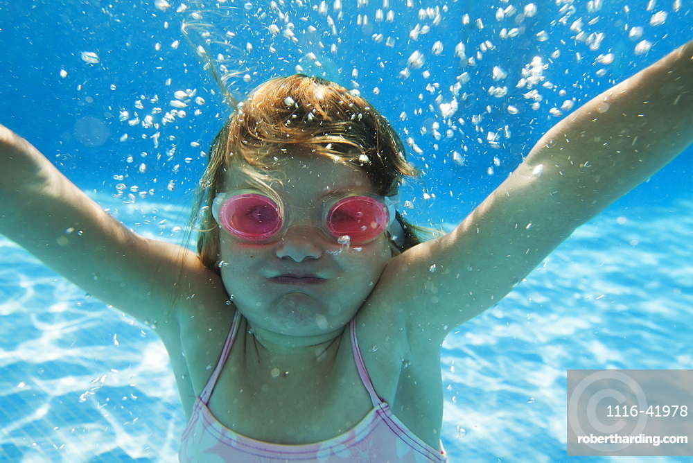 A girl swimming under the water in a pool with goggles on, Tarifa cadiz andalusia spain