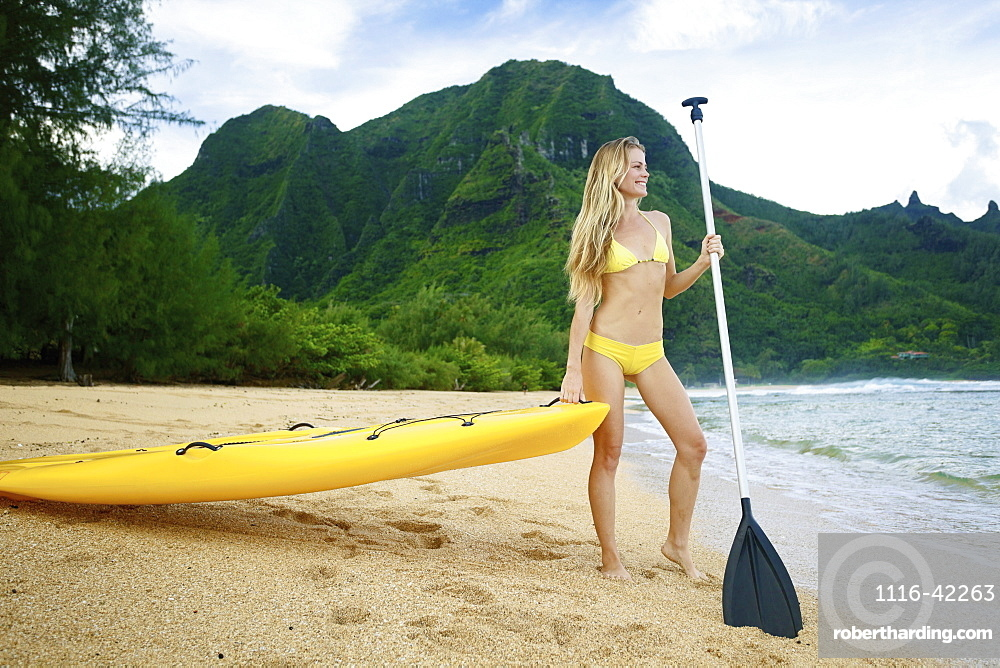 A Young Woman In A Yellow Bikini Stands At The Water's Edge With A Paddleboard And Paddle, Kauai, Hawaii, United States Of America