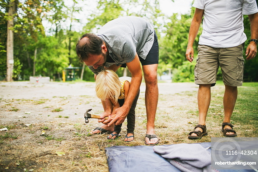 A Father And Young Daughter Work Together To Hammer In Tent Pegs At A Campsite, Peachland, British Columbia, Canada