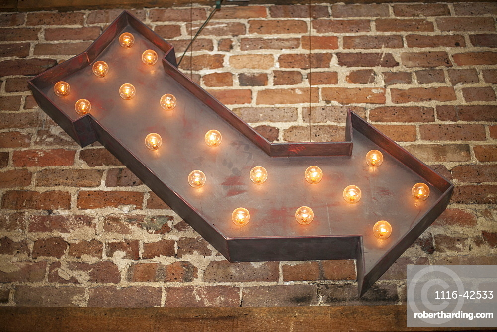 Lighted Metal Arrow Sign On Brick Wall, Starkville, Mississippi, United States Of America