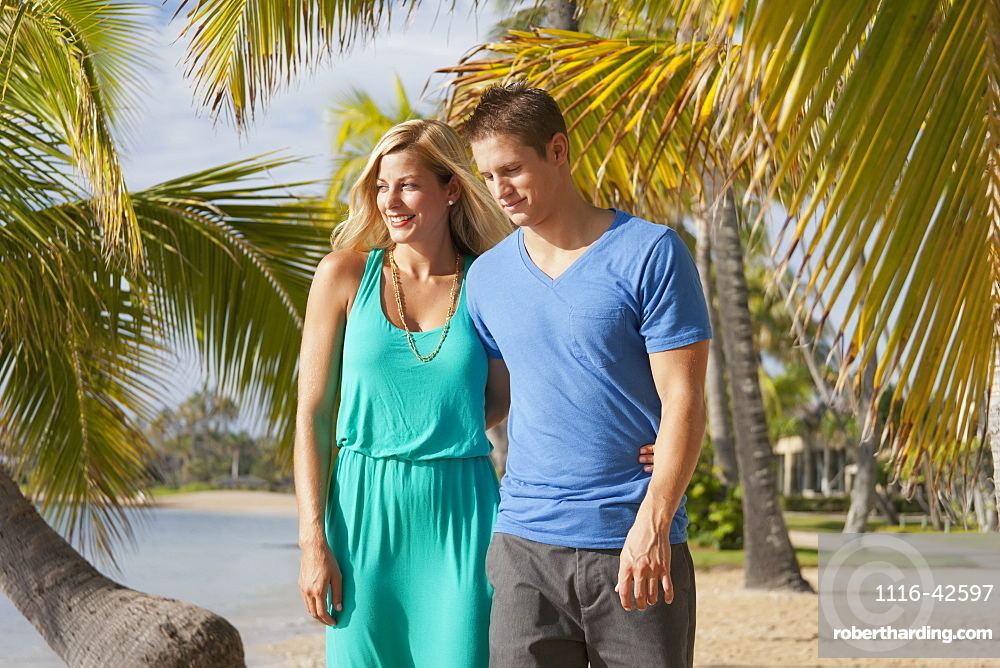 A Couple Walk On A Beach With Palm Trees Along The Water's Edge, Honolulu, Hawaii, United States Of America