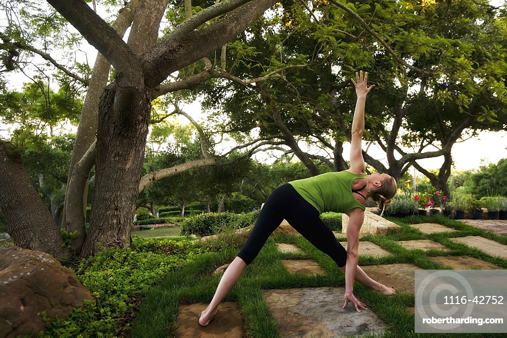 Woman In A Yoga Pose Stretching On Tiles By A Tree, California, United States Of America