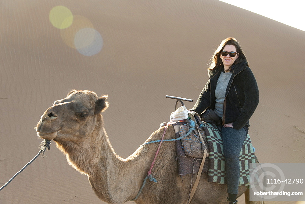 A woman riding a camel at the sand dunes, Souss-massa-draa morocco