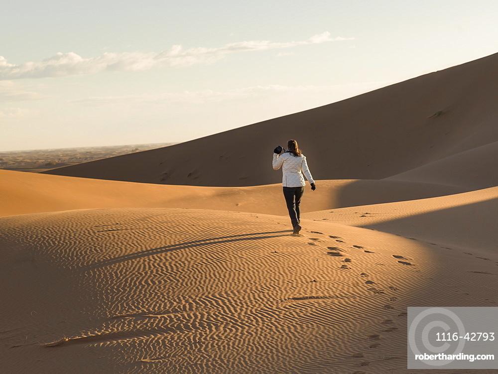 A woman walking on a sand dune, Sous-massa-draa morocco