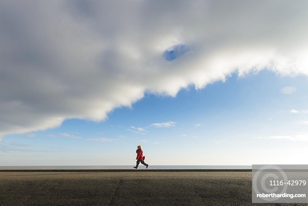 Boy Running Along Sea Wall, Aldeburgh, Suffolk, England