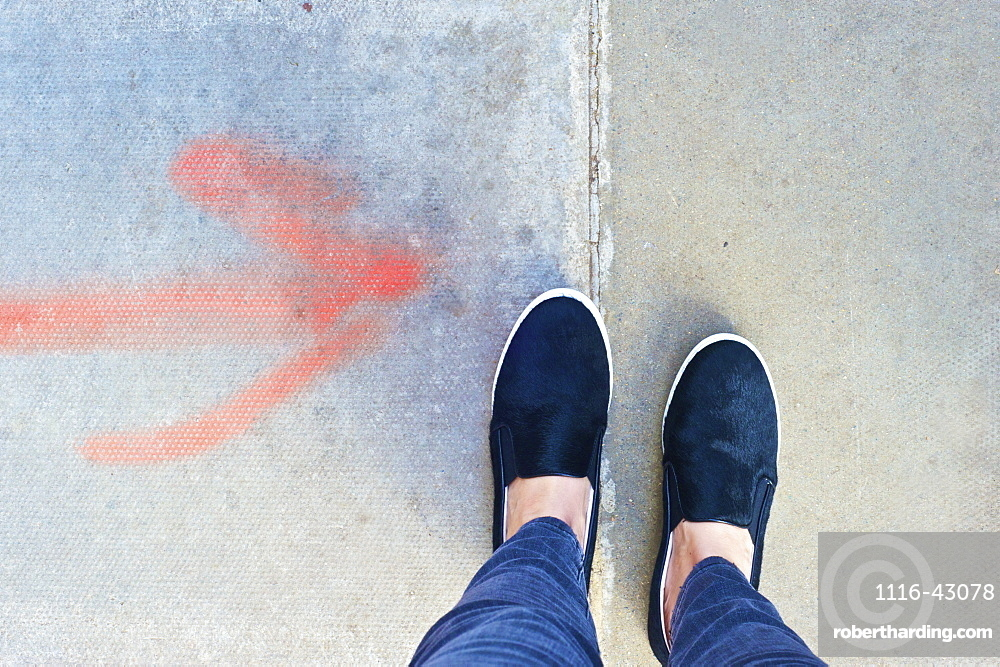 A Red Arrow Spray Painted On The Concrete Pointing To Feet, London, England