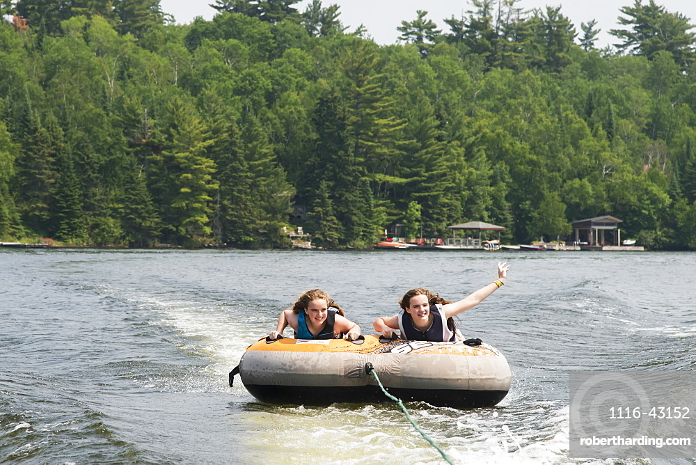Two Teenage Girls Riding An Inner Tube Being Pulled Behind A Boat In A Lake, Ontario, Canada