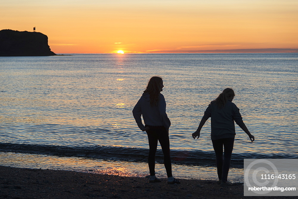 Silhouette Of Two Young Women On A Beach At The Water's Edge At Sunset, Trout River, Newfoundland, Canada