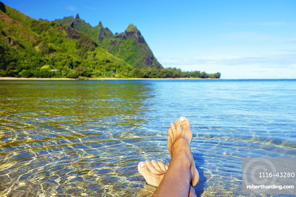 Bare Feet In The Clear Shallow Water Along The Coast Of An Hawaiian Island, Kauai, Hawaii, United States Of America