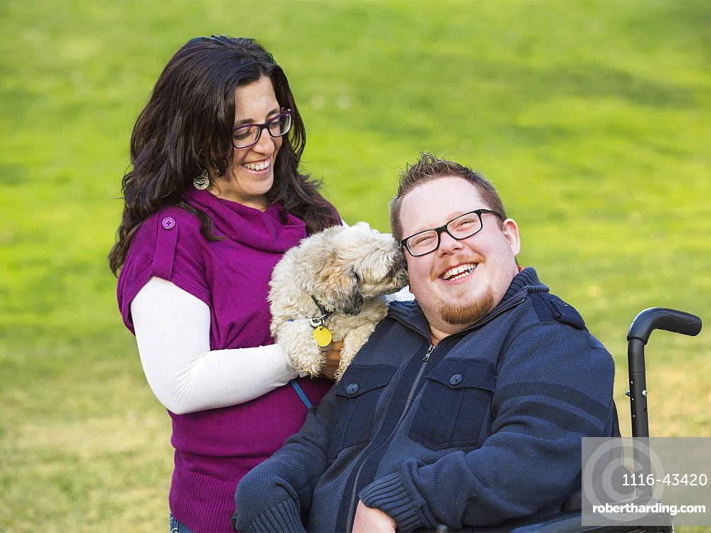 Disabled Husband With His Wife And Their Pet Dog In A Park In Autumn, Edmonton, Alberta, Canada