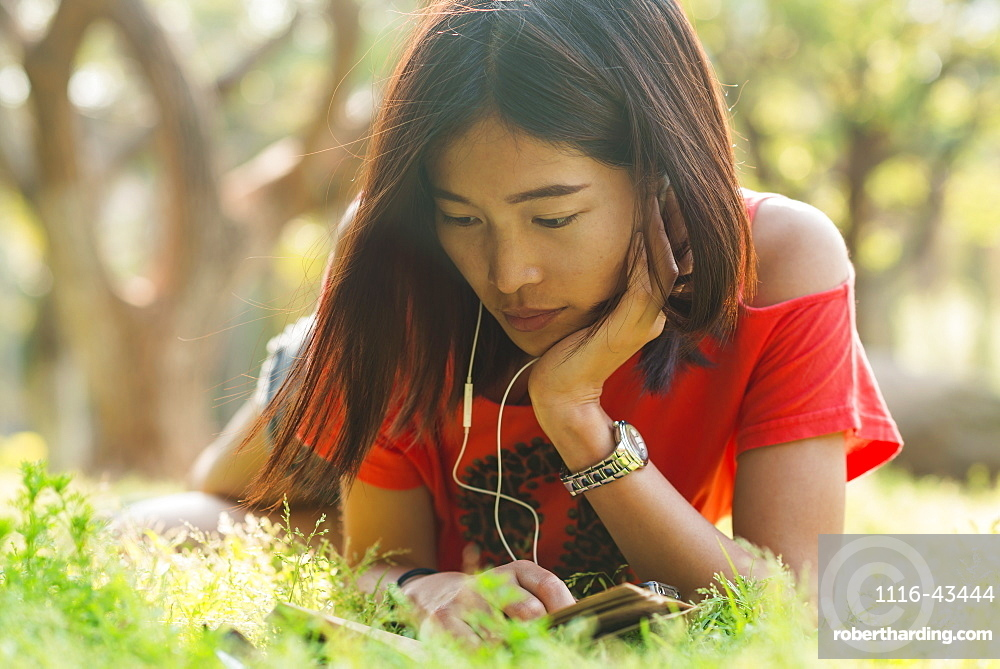 Chinese Girl Reading A Book And Listening To Music, Xiamen, Fujian Province, China