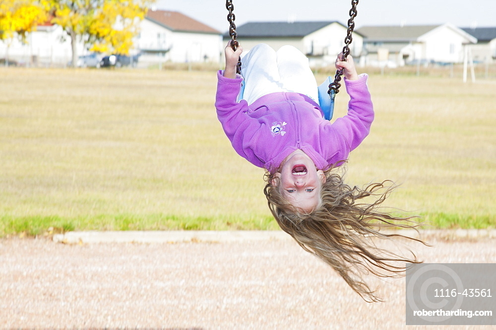 Young Girl On Swing In A Playground In Residential Community On A Cool, Windy Fall Day, Three Hills, Alberta, Canada