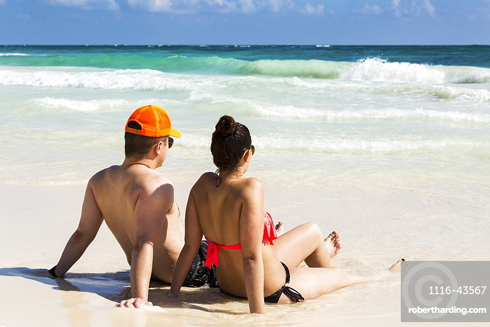 Couple Laying And Sitting On Sandy Beach With Waves Coming In And Blue Sky, Tulum, Quintana Roo, Mexico