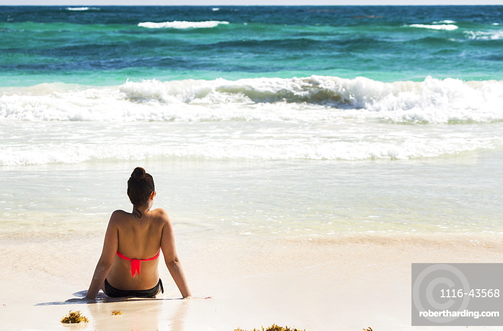 Young Woman Sitting On Sandy Beach In Water Looking Out At Waves Coming In And Blue Sky, Akumal, Quintana Roo, Mexico