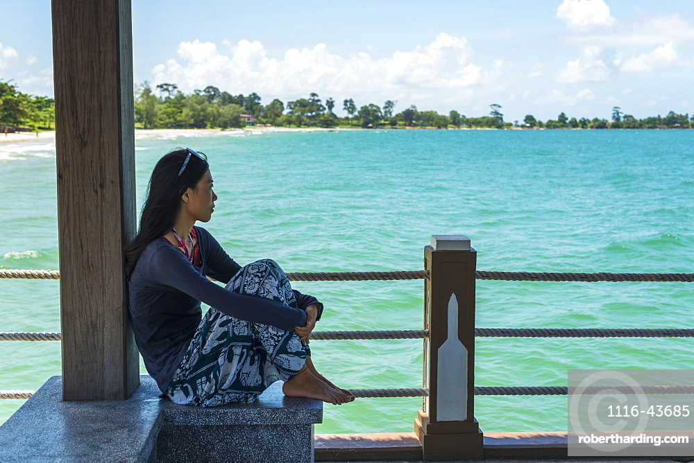 A Young Woman Sits On The Pier At Independence Beach, Sihanoukville, Cambodia