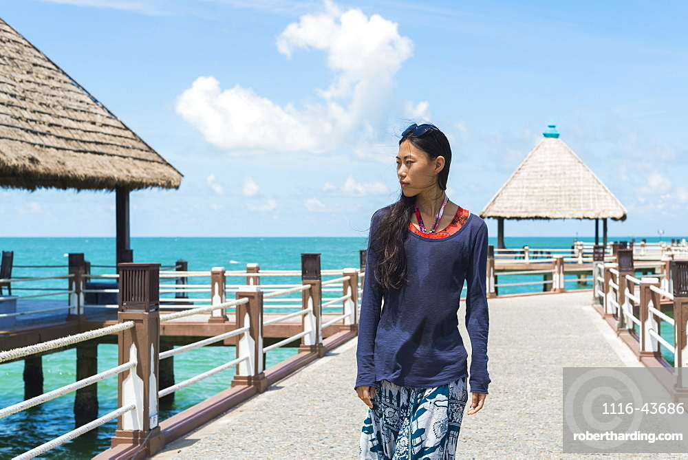 A Young Woman Walks On The Pier At Independence Beach, Sihanoukville, Cambodia