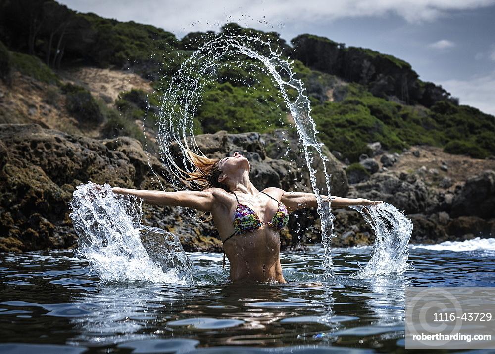 A Young Woman In A Bikini Splashing Water Along The Water's Edge, Tarifa, Cadiz, Andalusia, Spain