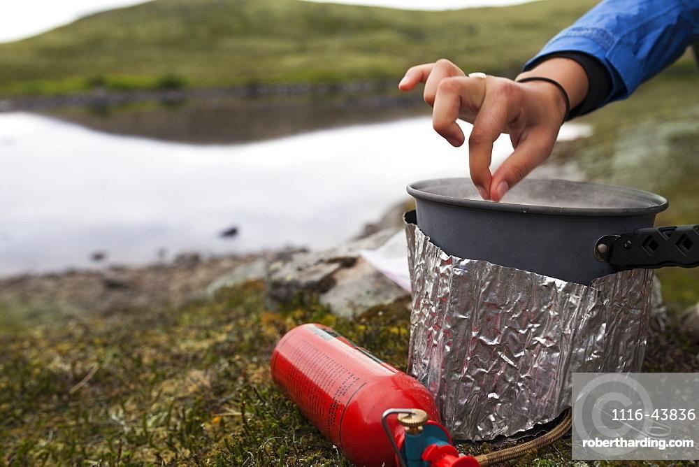 Female Backpacker Cooks With A Backpacker Camp Stove Near The Edge Of A Lake, Alaska