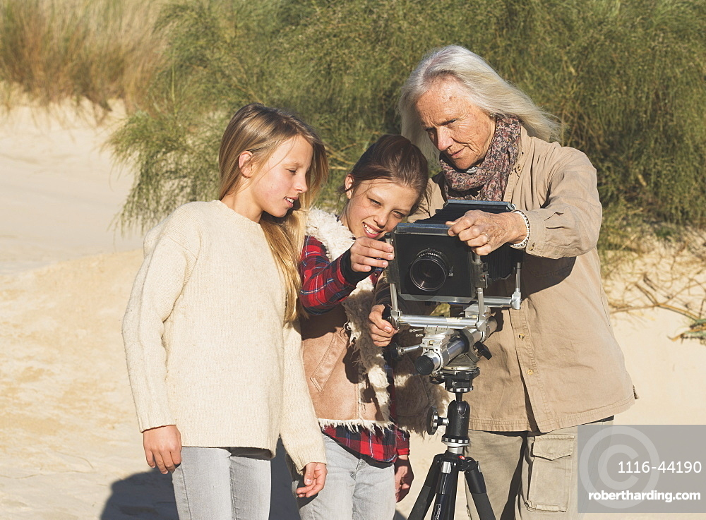 A Female Photographer Shows Two Young Girls Images On A Camera With Tripod On The Beach, Tarifa, Cadiz, Andalusia, Spain