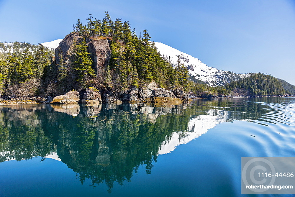 A Tall Outcropping Of Rocks And Evergreen Trees Reflects On The Waters Of Prince William Sound, Whittier, Alaska, United States Of America