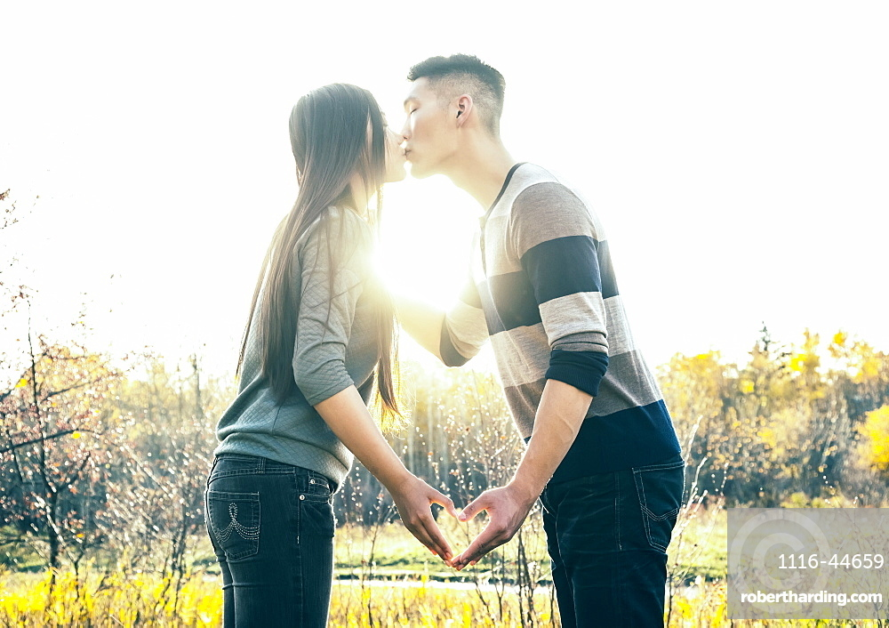 A Young Asian Couple Kissing In A Park In Autumn And Making A Heart With Their Hands In The Warmth Of The Setting Sun, Edmonton, Alberta, Canada