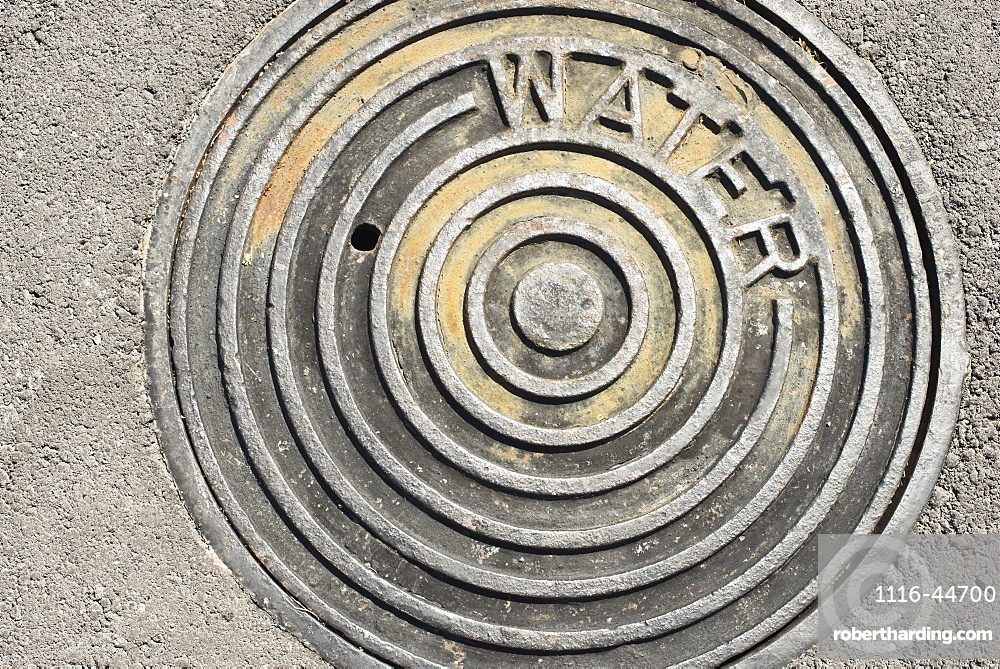 The Hot Sun Beats Down On A Manhole Cover With The Word 'water' Engraved On It, Waikaloa, Island Of Hawaii, Hawaii, United States Of America