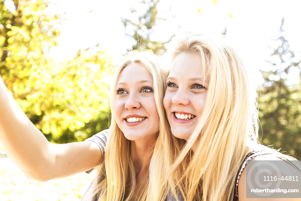 Two Sisters Having Fun In A City Park In Autumn And Talking A Selfie Of Themselves, Edmonton, Alberta, Canada