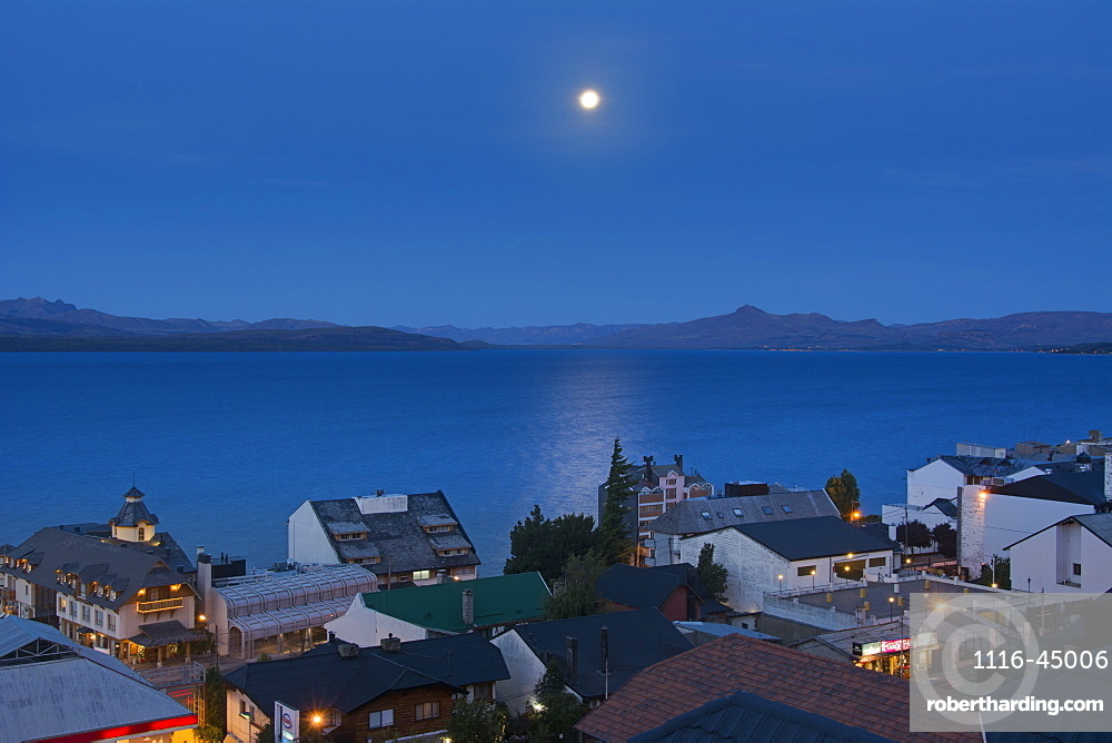The Moon Rising Over A Lake From Above The Town Roof Tops Showing Some Yellow City Lights Against The Blue Scene, Bariloche, Argentina