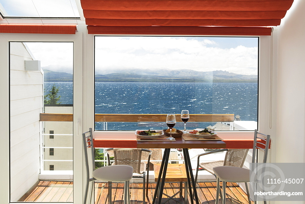 A Lunch Table With Two Glasses Of Red Wine Is Set In Front Of The Balcony Window Of A Bright Apartment With View Over A Lake, Bariloche, Argentina