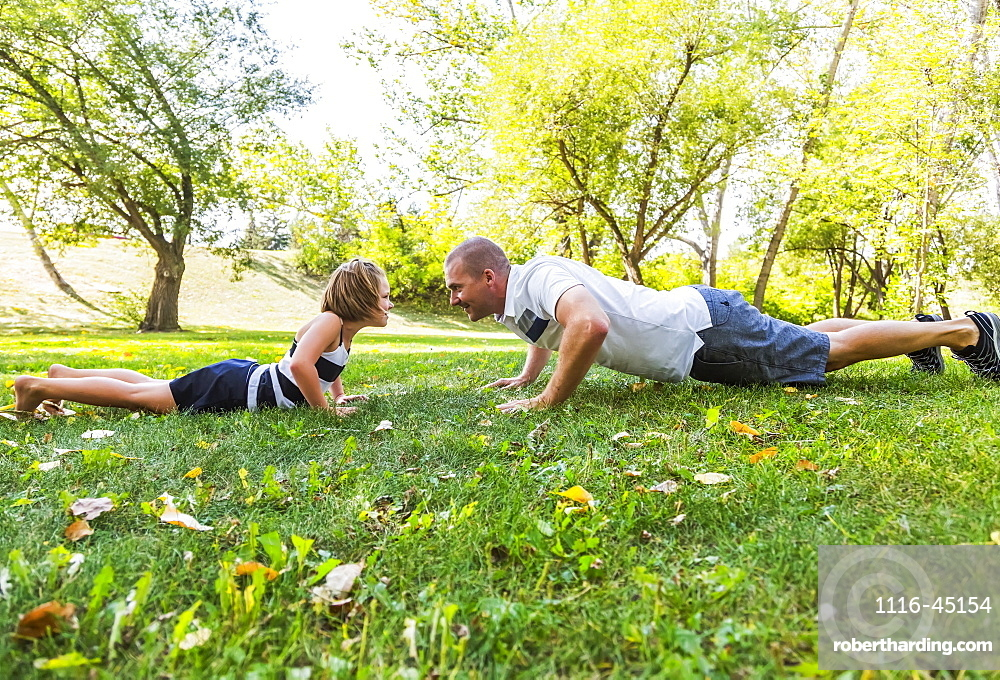 A Father And Daughter Staring Each Other Down In A Park During A Family Outing, Edmonton, Alberta, Canada