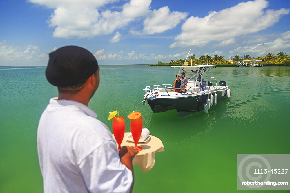 A Couple In A Boat Approaches A Dock Where A Server Is Waiting With Drinks, Saint Georges Caye Resort, Belize City, Belize