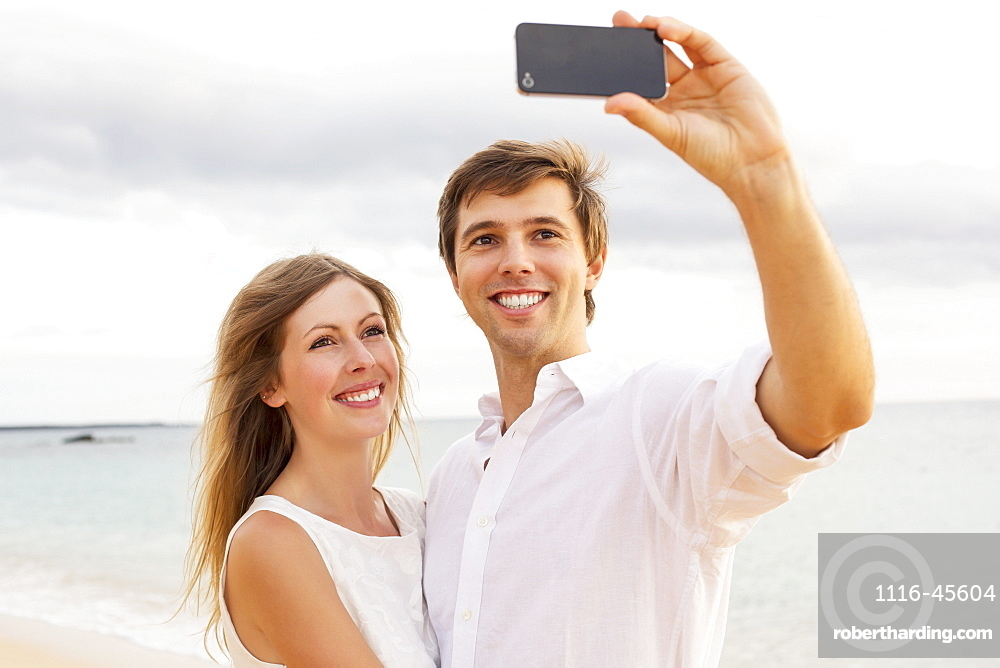 Happy Young Couple Taking A Selfie On The Beach At Sunset