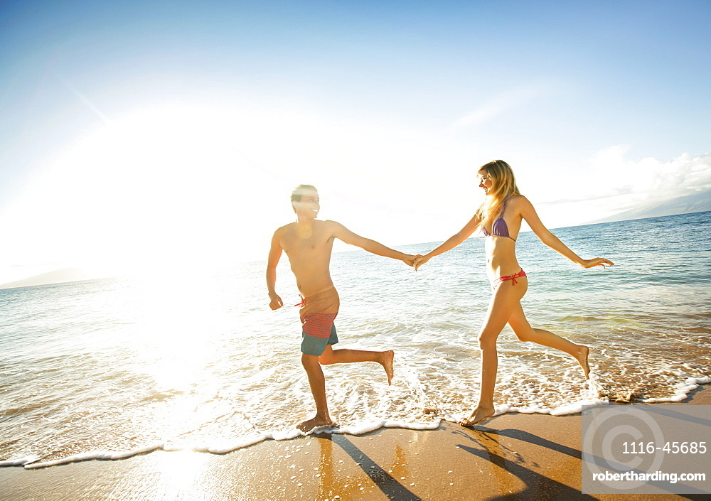 Happy Couple Running On A Tropical Beach In The Ocean At Sunset